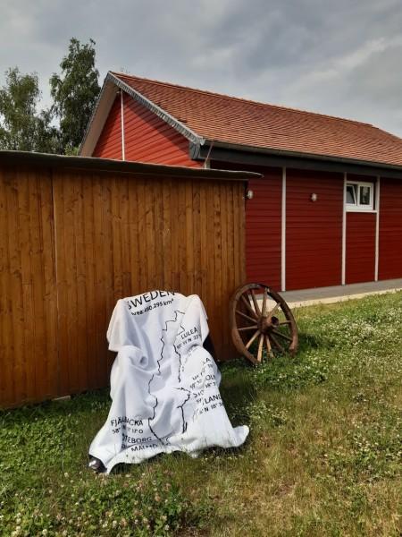 Kuscheldecke Schwedenkolter vor einem Schwedenhaus