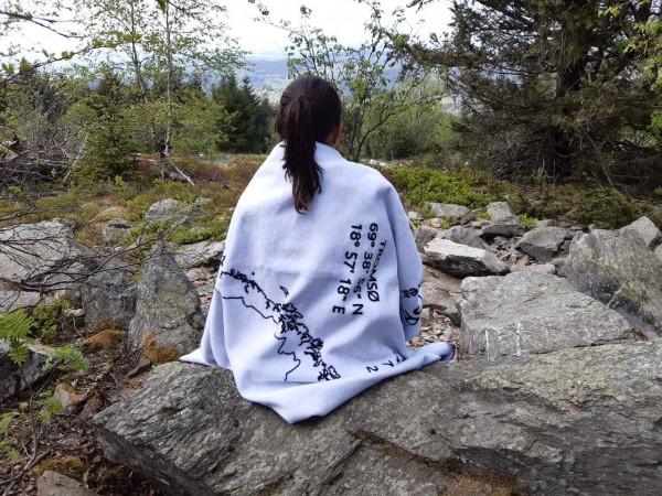 Frau sitzend mit Norwegen-Decke umgehaengt